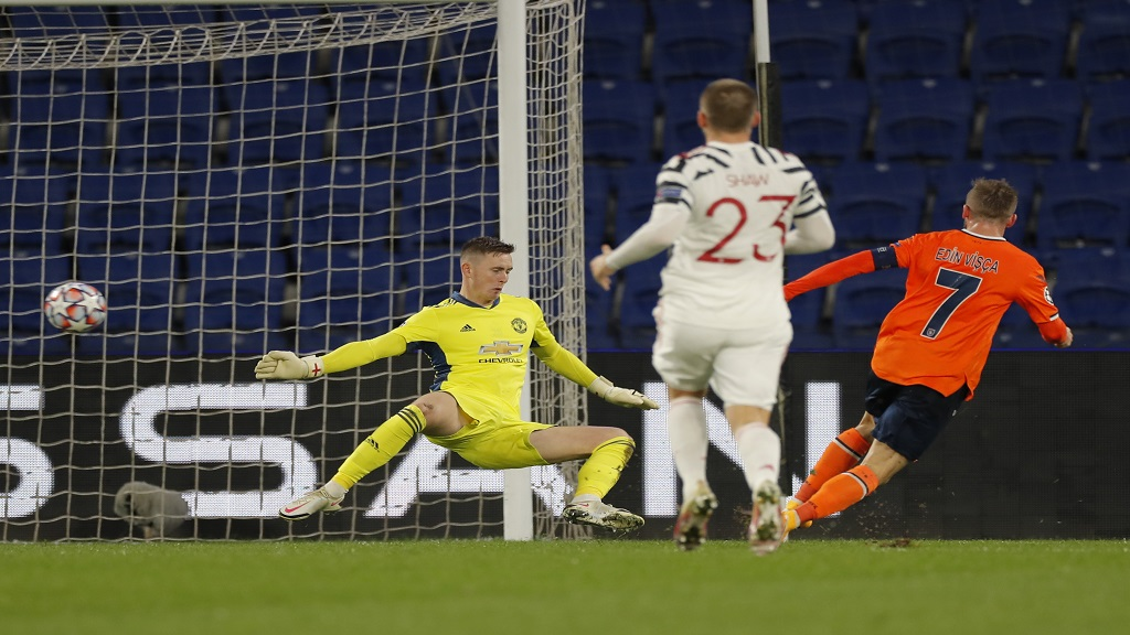 Manchester United's goalkeeper Dean Henderson, left, fails to save the ball as Basaksehir's Edin Visca, right, scores his side's second goal during a Champions League group H football match at the Fatih Terim stadium in Istanbul, Wednesday, Nov. 4, 2020. (AP Photo).
