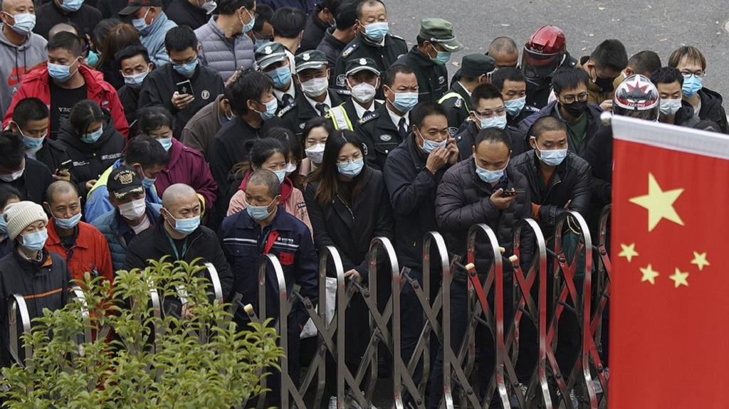 Airport workers wearing face masks to help curb the spread of the coronavirus wait for COVID-19 testing at the Shanghai Pudong International Airport in Shanghai, Monday, Nov. 23, 2020. Chinese authorities are testing millions of people, imposing lockdowns and shutting down schools after multiple locally transmitted coronavirus cases were discovered in three cities across the country last week. (AP Photo)