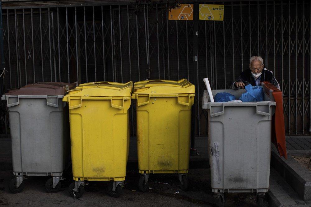 An elderly man searches through garbage bins in the southern neighbourhood of Vallecas, Madrid, Spain, on Thursday. (AP Photo/Bernat Armangue)