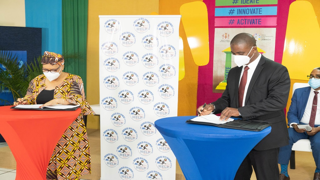 Chief Executive Officer of the JBDC, Valerie Veira (left) and Caribbean Business Consultant for CIAL Dun & Bradstreet, Kavin Hewitt sign the MSME development agreement during the recent signing session.