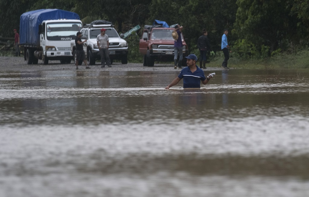 A man walks through a flooded road in Okonwas, Nicaragua, Wednesday, November 4, 2020. Eta weakened from the Category 4 hurricane to a tropical storm after lashing Nicaragua's Caribbean coast for much of Tuesday, its floodwaters isolating already remote communities and setting off deadly landslides. (AP Photo/Carlos Herrera)