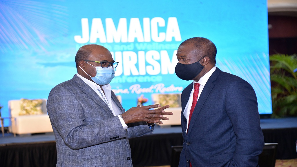 Tourism Minister, Edmund Bartlett (left) and Jamaica Hotel and Tourist Association (JHTA) President, Clifton Reader, engage in one-on-one discussion regarding the way forward for health and wellness as a key factor in driving tourism in Jamaica, at Wednesday's opening of the Jamaica Health and Wellness Tourism Conference at the Montego Bay Convention Centre.