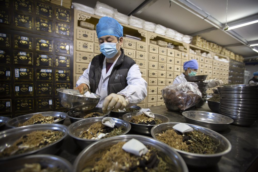Workers fill orders for prescriptions at the Bo Ai Tang traditional Chinese medicine clinic in Beijing. With no approved drugs for the new coronavirus, some people are turning to alternative medicines, often with governments promoting them. (AP Photo/Mark Schiefelbein)