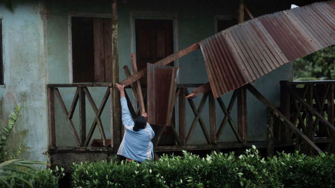 A woman works to recover the part of the roof damaged by Hurricane Eta in Wawa, Nicaragua, Tuesday, November 3, 2020. Eta slammed into Nicaragua's Caribbean coast with potentially devastating winds Tuesday, while heavy rains thrown off by the Category 4 storm already were causing rivers to overflow across Central America. (AP Photo/Carlos Herrera)