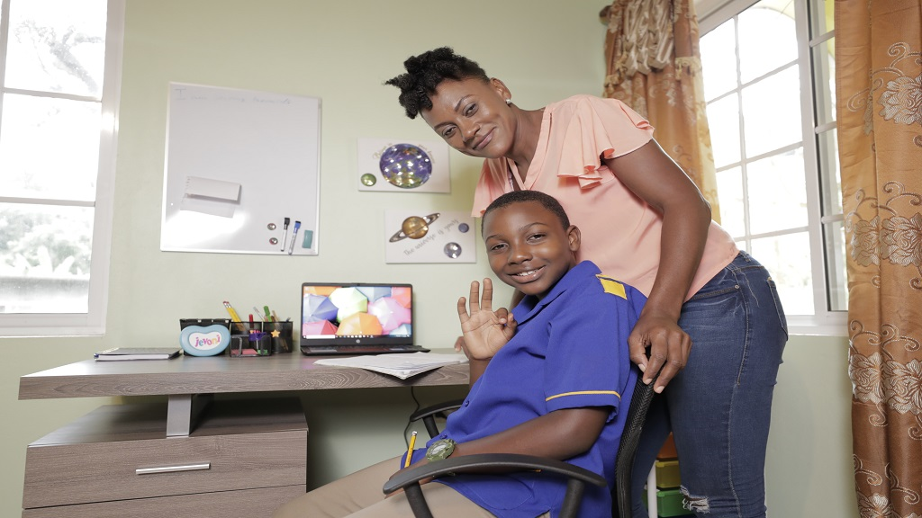 A beaming Jevoni Campbell and his mother Nickeisha, pause for a photo by the 'learning corner' contributed by Sagicor Bank to improve his online learning experience. Jevoni received a desk, laptop computer and internet connection for one year courtesy of the financial institution.