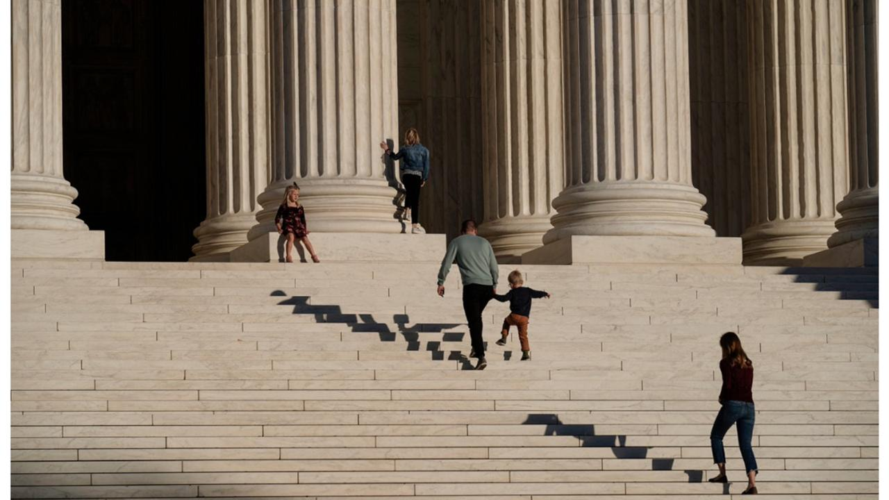 A family visits the Supreme Court in Washington, Wednesday, November 4, 2020. The Trump campaign is seeking to intervene in a Pennsylvania case at the Supreme Court that deals with whether ballots received up to three days after the election can be counted. (AP Photo/J. Scott Applewhite)