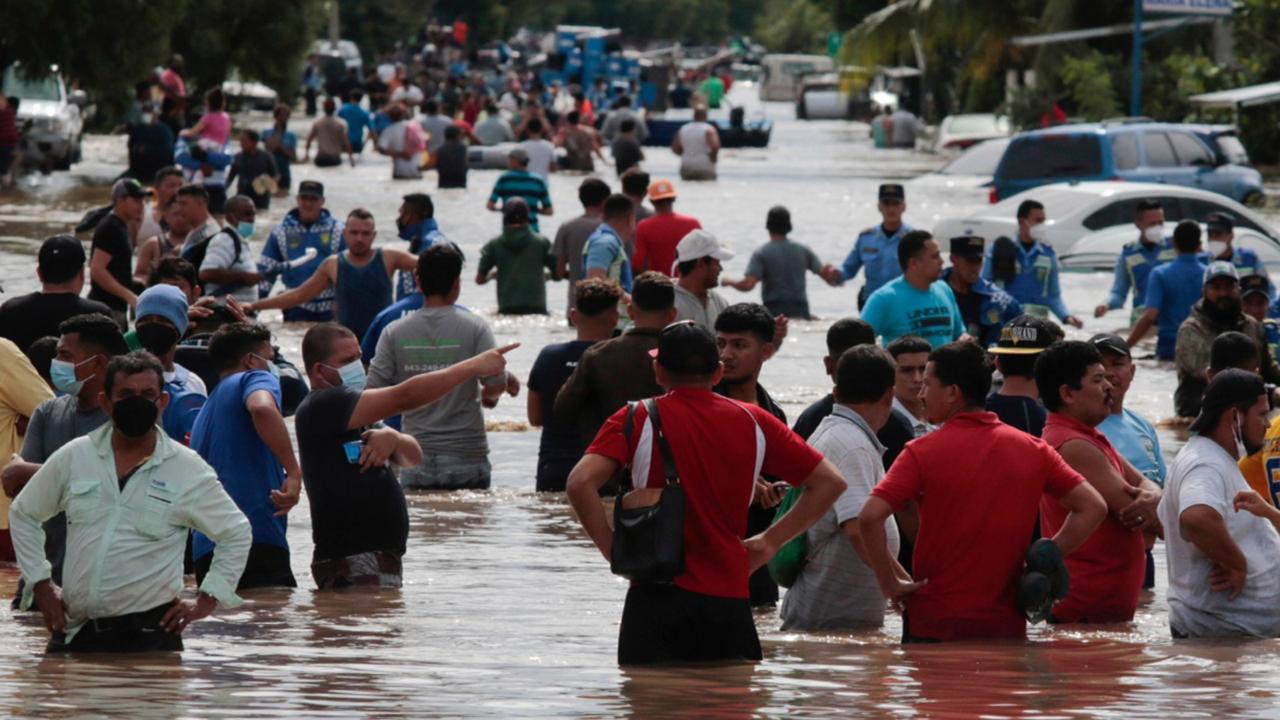 Residents wade through a flooded road in the aftermath of Hurricane Eta in Planeta, Honduras, Thursday, November 5, 2020. (AP Photo/Delmer Martinez)