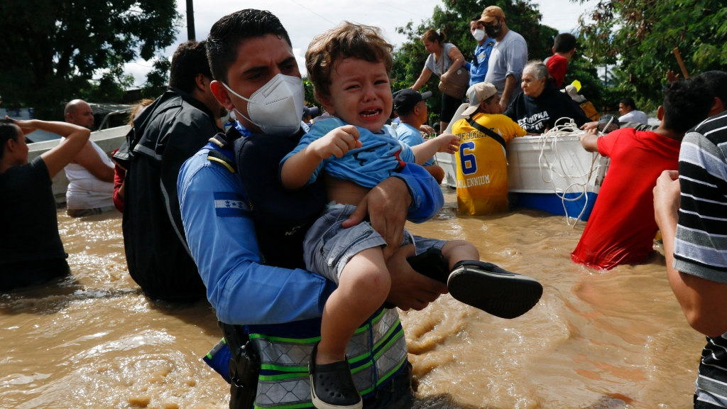 A toddler is carried over a flooded street in the aftermath of Hurricane Eta in Jerusalen, Honduras, Thursday, November 5, 2020. The storm that hit Nicaragua as a Category 4 hurricane on Tuesday had become more of a vast tropical rainstorm, but it was advancing so slowly and dumping so much rain that much of Central America remained on high alert. (AP Photo/Delmer Martinez)