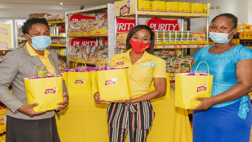 Russanette Dennis (centre), marketing representative of Consolidated Bakeries handing over products to Taneka McKoy Phipps (left) who is spearheading the Blackboard Initiative. Also pictured is McKoy Phipps' daughter Sherece.