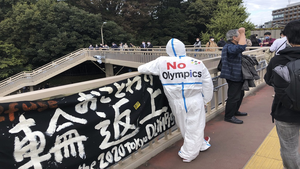 An anti-Olympic protester stands outside the Yoyogi National Stadium in Tokyo on Sunday, Nov. 8, 2020. About 30 anti-Olympic protesters showed up Sunday outside the gymnastic event. (AP Photo/Stephen Wade).