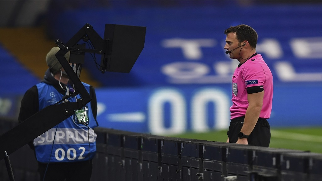 A referee watches an incident on the VAR screen before awarding a penalty to Chelsea during the Champions League Group E football match against Rennes at Stamford Bridge, London, England, Wednesday Nov. 4, 2020. (Ben Stansall/Pool via AP).