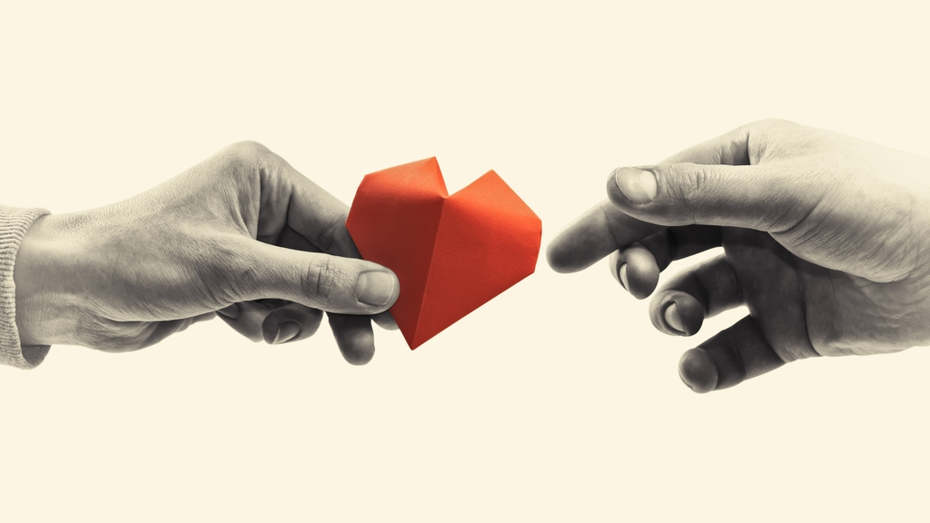Red heart in woman and man hands. Black and white image. Concept of love, giving gifts, donorship. Photo: SvetaZi on iStock