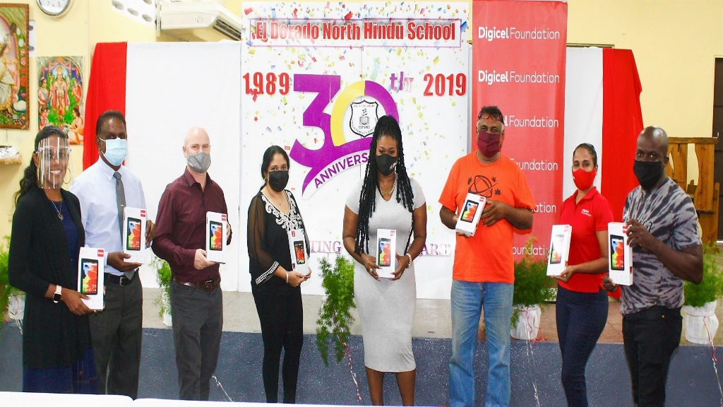 (L-R): Cherry-ann Douglas, Principal, Mahindranath Maharaj, President of the Parent Teachers Committee, David Douglas, Vice Principal, Nalini Ramdhanie, Digicel endorsee, Nadia Batson, Parent, Adesh Ramlochan, Digicel Foundation Project Co-ordinator Diana Mathura-Hobson and Parent Sean Lewis proudly displays some of the devices being donated to the students of El Dorado North Hindu School by the Digicel Foundation.
