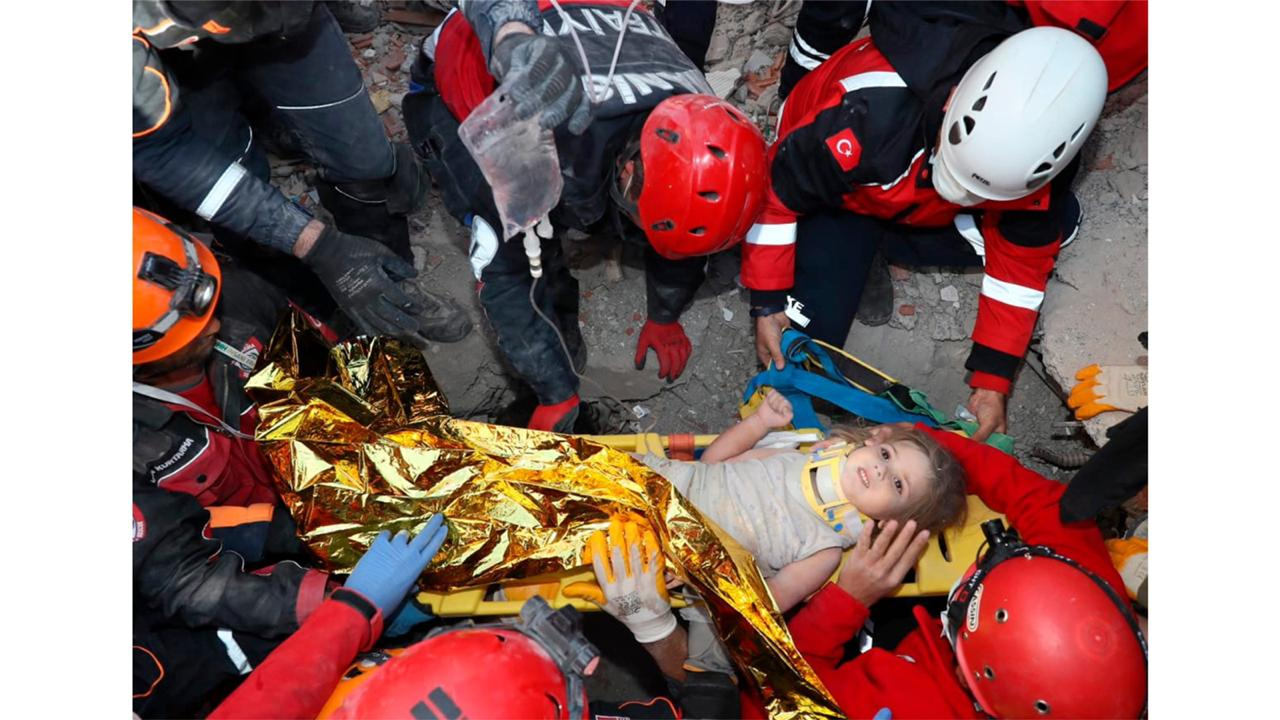 In this photo provided by the government's Search and Rescue agency AFAD, rescue workers, who were trying to reach survivors in the rubble of a collapsed building, surround Ayda Gezgin in the Turkish coastal city of Izmir, Turkey, Tuesday, November 3, 2020, after they have pulled the young girl out alive from the rubble of a collapsed apartment building four days after a strong earthquake hit Turkey and Greece. (AFAD via AP)