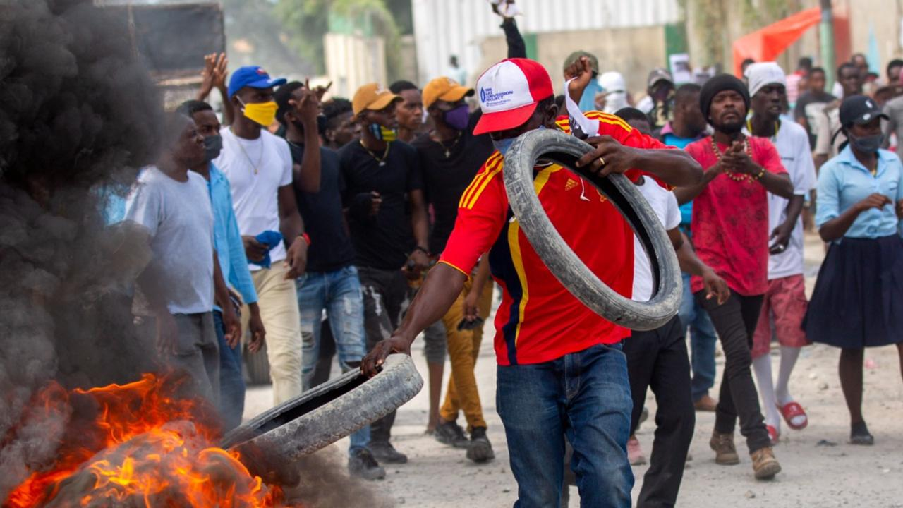 A protester adds tires to a burning barricade during a protest march to demand answers after the kidnapping and murder of high school senior Evelyne Sincère, in Port-au-Prince, Haiti, Thursday, November 5, 2020. (AP Photo/Dieu Nalio Chery)