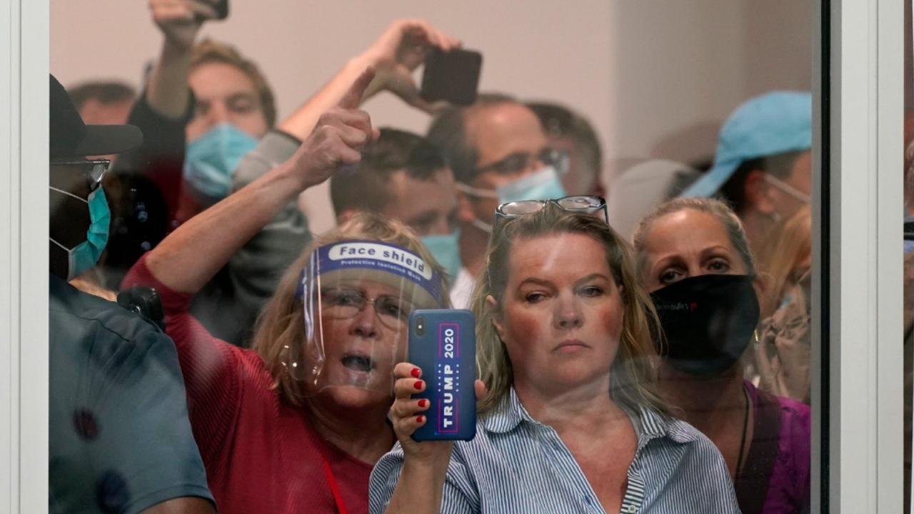 People wanting to be election challengers yell as they look through the windows of the central counting board as police were helping to keep additional challengers from entering due to overcrowding, Wednesday, November 4, 2020, in Detroit. (AP Photo/Carlos Osorio)