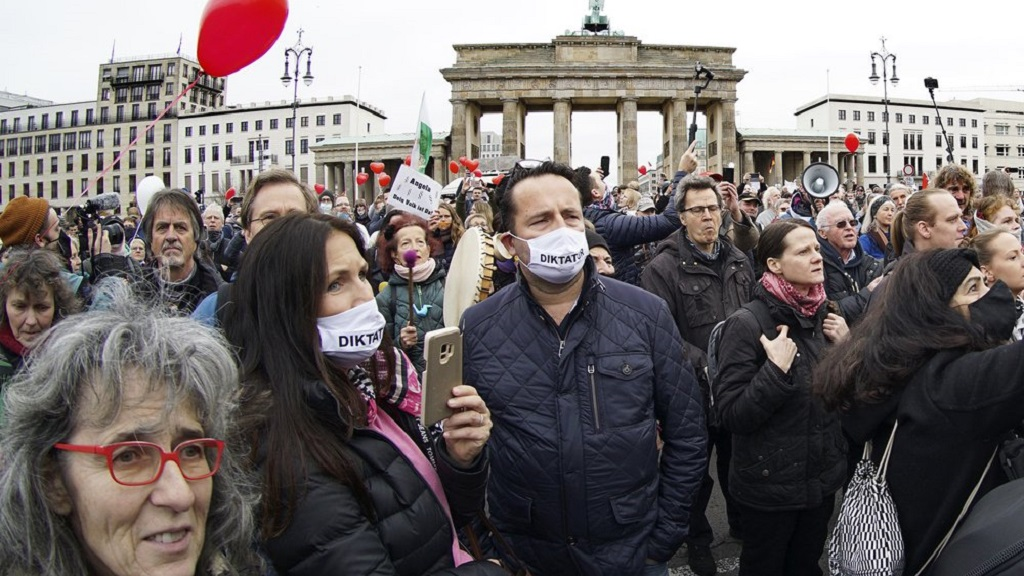 People attend a protest rally in front of the Brandenburg Gate in Berlin, Germany, Wednesday, Nov. 18, 2020 against the coronavirus restrictions in Germany. Police in Berlin have requested thousands of reinforcements from other parts of Germany to cope with planned protests by people opposed to coronavirus restrictions. Word on the mask reads 'Dictatorship'. (AP Photo/Michael Sohn)
