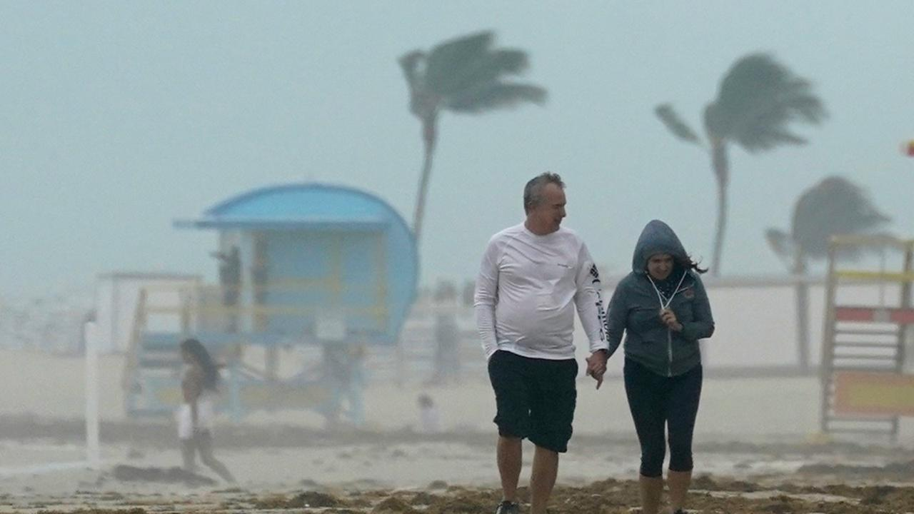 A couple walks along the beach during a downpour, Sunday, November 8, 2020, on Miami Beach, Florida's famed South Beach.  (AP Photo/Wilfredo Lee)