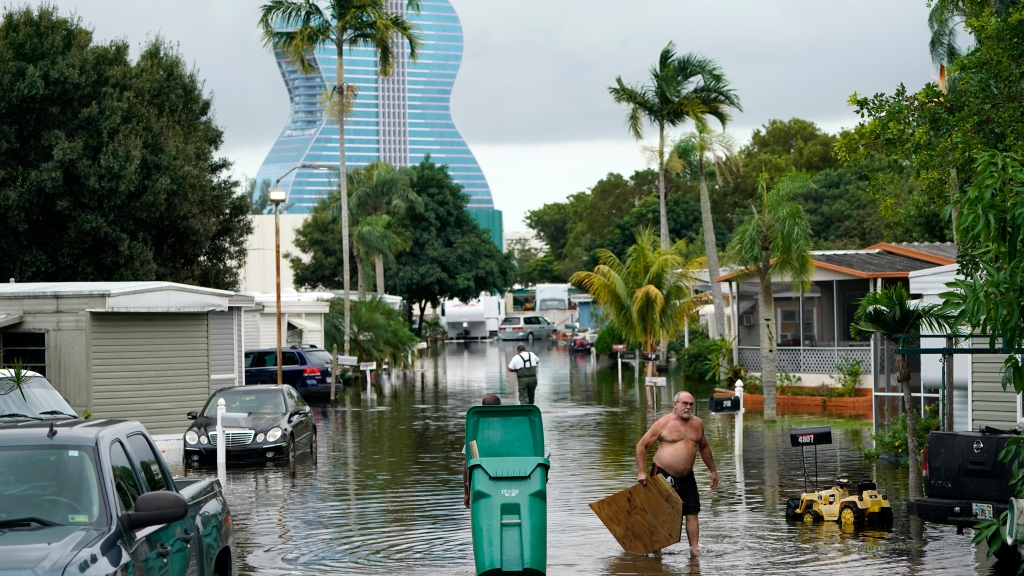 Residents clear debris from a flooded street in the Driftwood Acres Mobile Home Park in the shadow of the Guitar Hotel at Seminole Hard Rock, in the aftermath of Tropical Storm Eta, Tuesday, Nov. 10, 2020, in Davie, Fla. Tropical Storm Eta was squatting off western Cuba on Tuesday after drifting away from South Florida, where it unleashed a deluge that flooded entire neighborhoods and covered the floors of some homes and businesses. Photo: AP Photo/Lynne Sladky