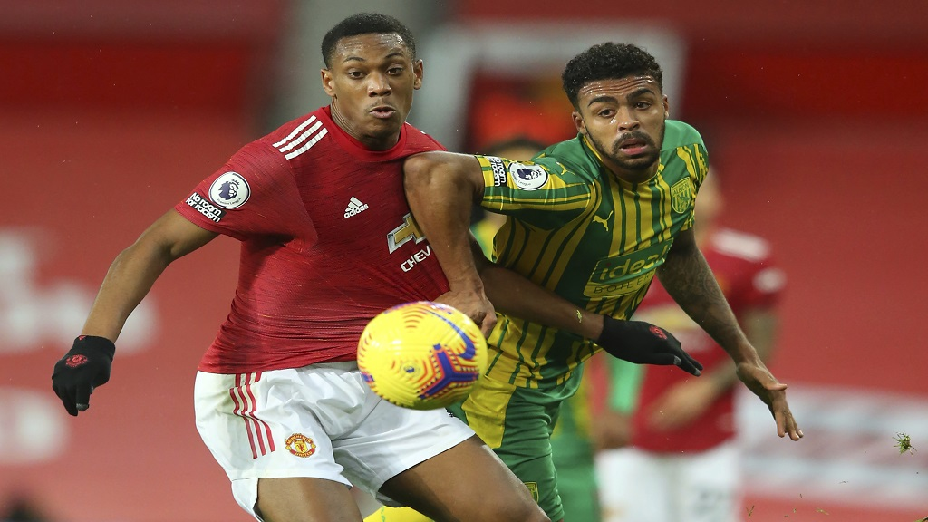 Manchester United's Anthony Martial, left, and West Bromwich Albion's Darnell Furlong fight for the ball during their English Premier League football match at the Old Trafford stadium in Manchester, England, Saturday, Nov. 21, 2020. (Alex Livesey/Pool via AP).