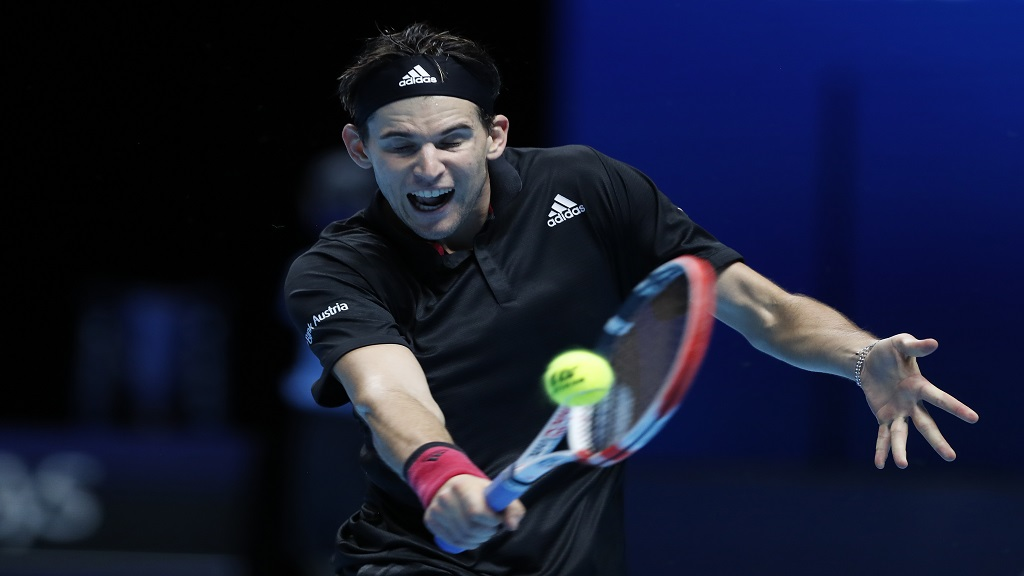 Dominic Thiem of Austria plays a return to Rafael Nadal of Spain during their singles tennis match at the ATP World Finals tennis tournament at the O2 arena in London, Tuesday, Nov. 17, 2020. (AP Photo/Frank Augstein).