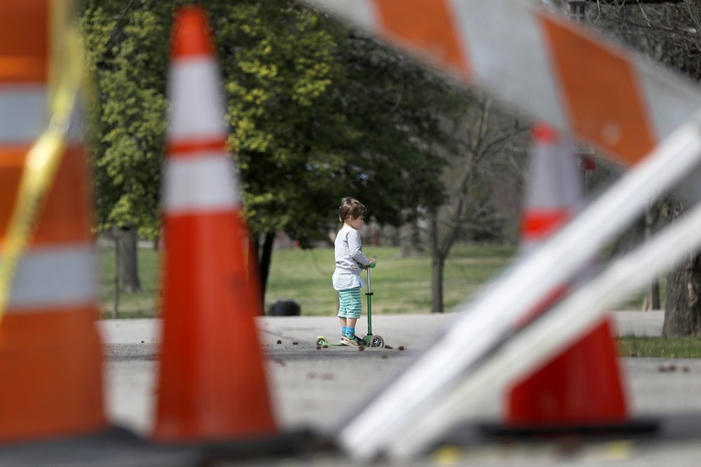 A child rides a scooter past barricades at an entrance to Tower Grove Park in St Louis, Missouri. The entrance to the park has been closed to vehicle traffic in an effort to give visitors on foot more room to practice social distancing and help slow the spread of the coronavirus. (AP Photo/Jeff Roberson)