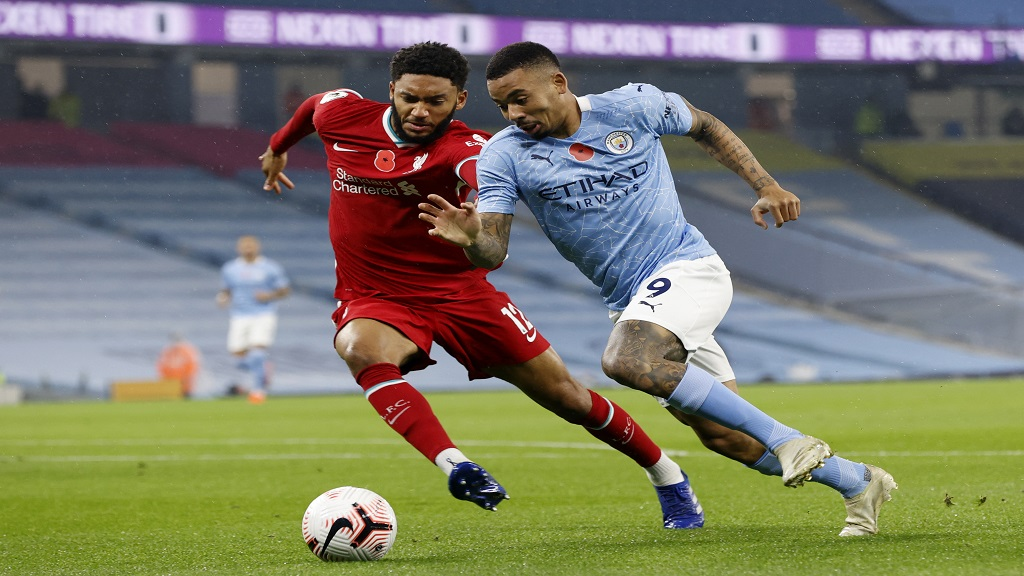 Liverpool's Joe Gomez, left, vies for the ball with Manchester City's Gabriel Jesus during an English Premier League football match at the Etihad stadium in Manchester, England, Sunday, Nov. 8, 2020. (Clive Brunskill/Pool via AP).