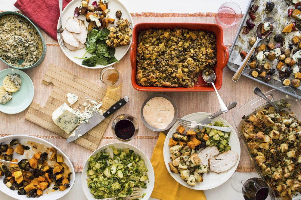 This October 2017 photo taken in New York, shows a Thanksgiving spread with hot spinach and mushroom dip, turkey, cornbread stuffing and sauteed brussel sprouts. A meal like this can be cooked and readied to be enjoyed in multiple homes and connected virtually, during this year's Thanksgiving holiday. (Sarah Crowder/Katie Workman via AP)