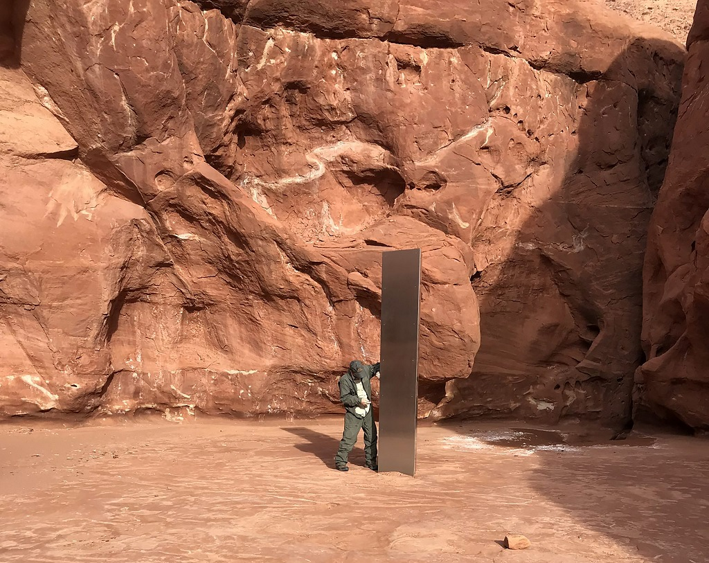 This November 18, 2020 photo provided by the Utah Department of Public Safety shows a Utah state worker inspecting a metal monolith that was found installed in the ground in a remote area of red rock in Utah. (Utah Department of Public Safety via AP)