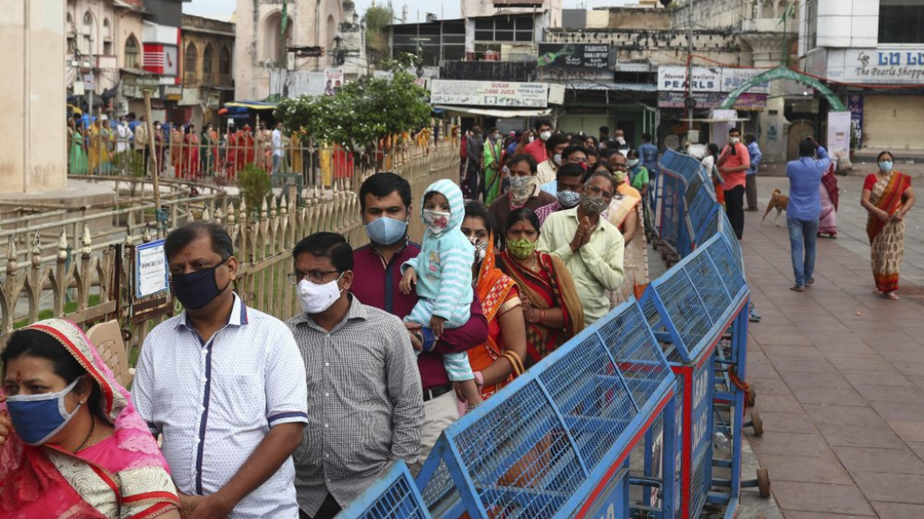 Indians wearing face masks as a precaution against the coronavirus stand in a queue to offer prayers at Bhagyalaxmi temple near Charminar ahead of Diwali, the festival of lights, in Hyderabad, India, Thursday, Nov. 12, 2020. Health officials have warned about the potential for the coronavirus to spread during the upcoming religious festival season, which is marked by huge gatherings in temples and shopping districts. (AP Photo/Mahesh Kumar A.)