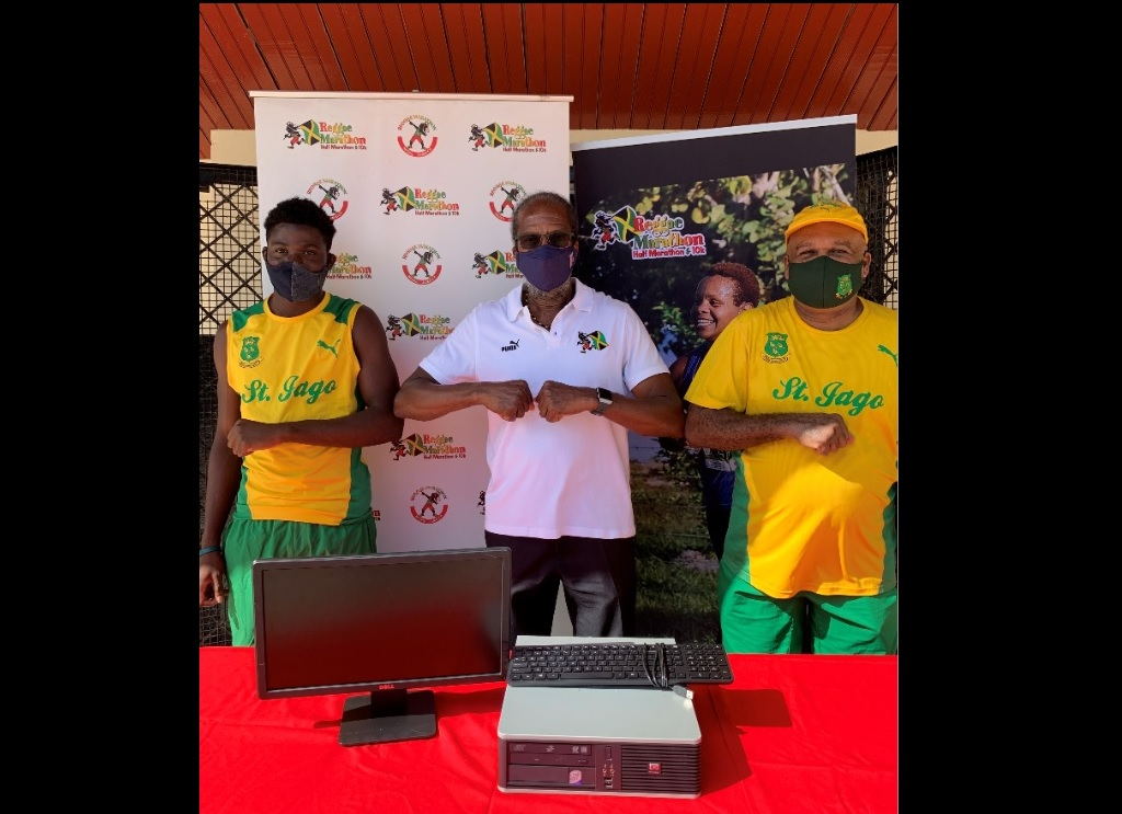 Tafar-Hi Hinds ( left) of St Jago and coach Michael Feurtado (right) acknowledge the donation of  three computers from Reggae Marathon race director Alfred Francis (centre).