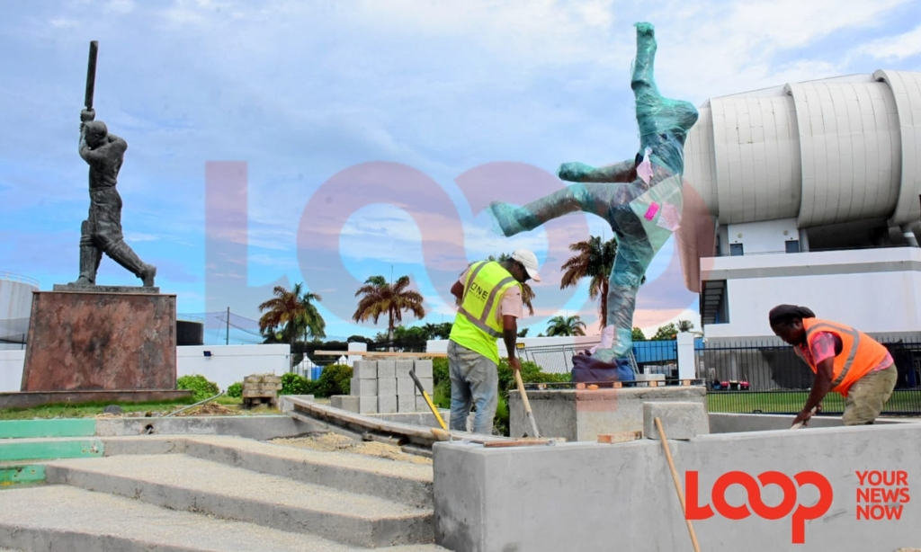 Workers completing the placement and setting of the new statue beside Sir Garfield Sobers' statue outside Kensington Oval on November 13.
