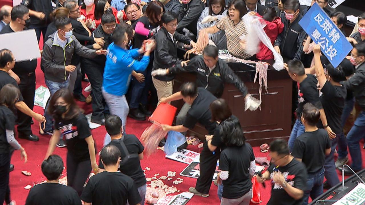 """In this image made from video, lawmakers fight during a parliament session in Taipei, Taiwan, Friday, November 27, 2020. Taiwan's lawmakers got into a fistfight and threw pig guts at each other Friday over a soon-to-be enacted policy that would allow imports of US pork and beef."""" (FTV via AP)"""