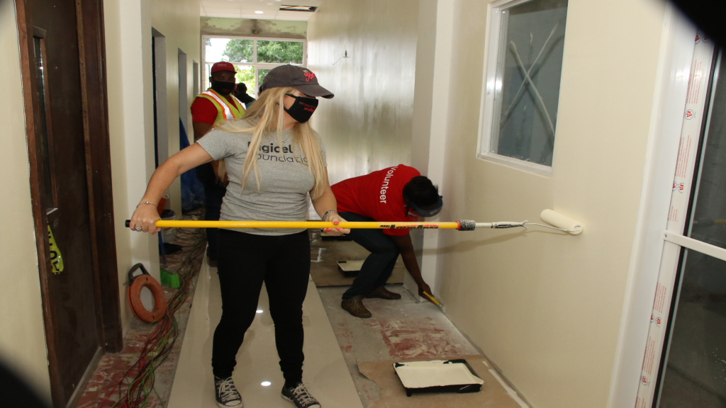 Digicel staff members painting the interior of the Colm Delves Centre last Thursday.