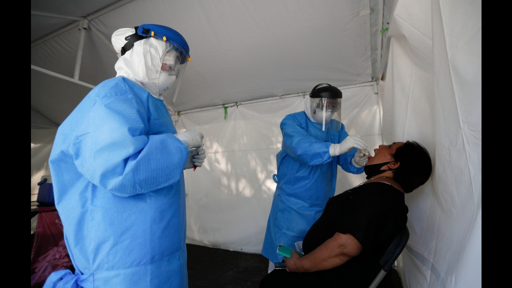 A healthcare worker collects a sample to test for the new coronavirus inside a mobile diagnostic tent, in the Coyoacan district of Mexico City, Friday, November 13, 2020. Mexico City announced Friday it will order bars closed for two weeks after the number of people hospitalized for COVID-19 rose to levels not seen since August. Photo: AP Photo/Eduardo Verdugo