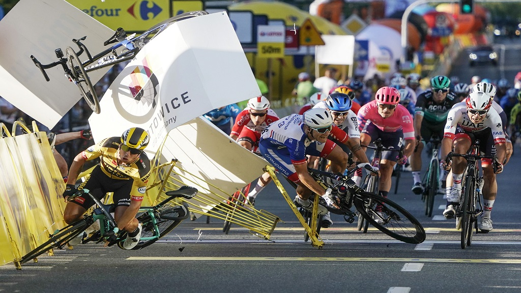 In this Aug. 5, 2020 file photo, Dutch cyclist Dylan Groenewegen crashes to the ground as a bicycle is flying overhead in a major collision on the final stretch of the opening stage of the Tour de Poland race in Katowice, Poland.  (AP Photo/Tomasz Markowski).