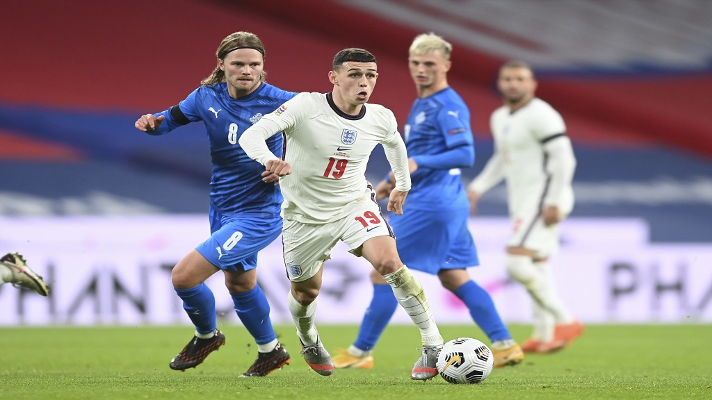 England's Phil Foden, centre, and Iceland's Birkir Bjarnason challenge for the ball during an UEFA Nations League football match at Wembley stadium in London, Wednesday, Nov. 18, 2020. (Michael Regan/Pool via AP).