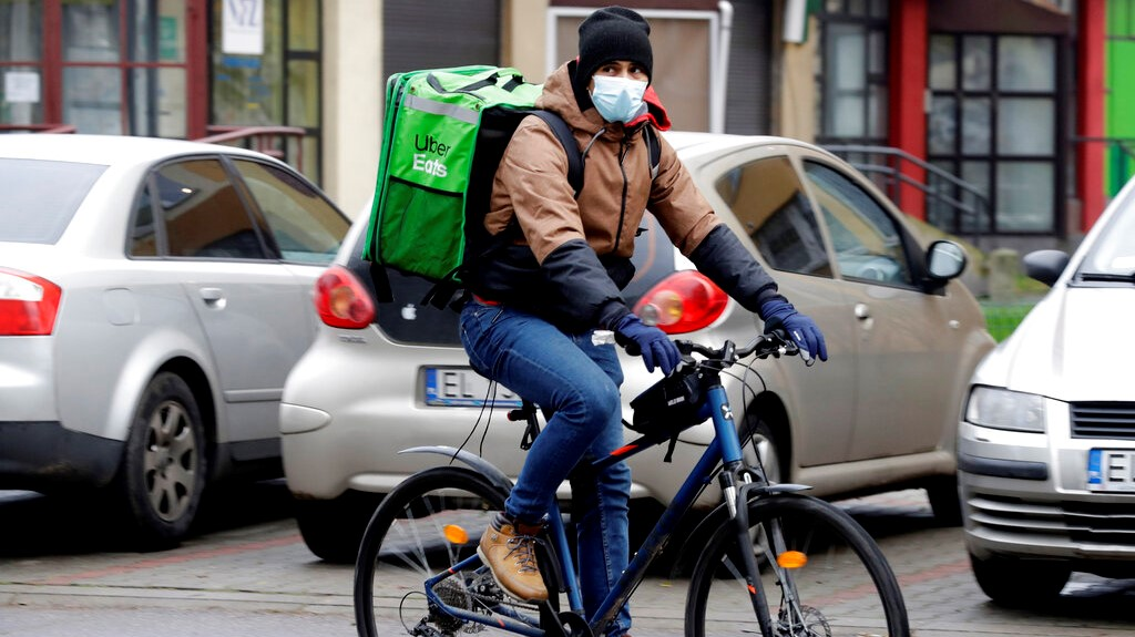 Venezuela's 2012 Olympic champion in fencing, Ruben Limardo Gascon, cycles with a food delivery to clients in Lodz, Poland, Saturday, Nov. 14, 2020. (AP Photo/Czarek Sokolowski)