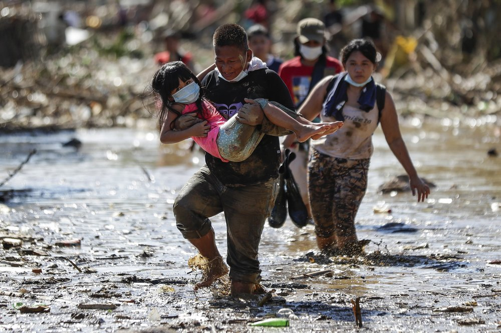 A man carries a girl through debris and floods in the typhoon-damaged Kasiglahan village in Rodriguez, Rizal province, Philippines on Friday, Nov. 13, 2020. Thick mud and debris coated many villages around the Philippine capital Friday after Typhoon Vamco caused extensive flooding that sent residents fleeing to their roofs and killing dozens of people. (AP Photo/Aaron Favila)