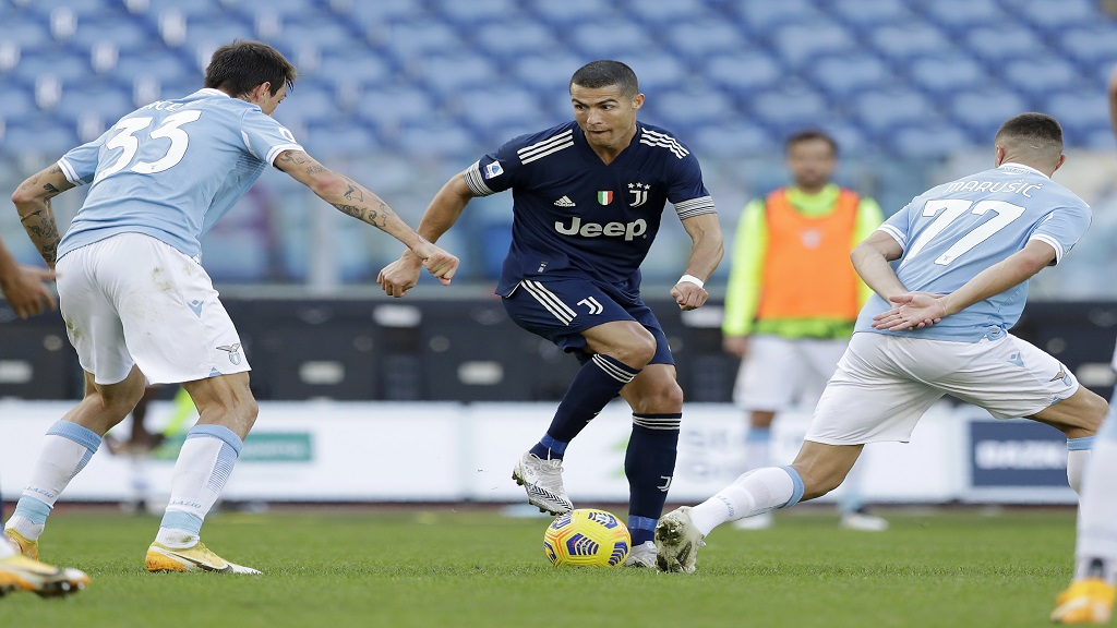 Juventus' Cristiano Ronaldo, centre, tries to dribble past Lazio's Francesco Acerbi, left, and Adam Marusic during a Serie A football match at the Olympic stadium in Rome, Sunday, Nov. 8, 2020. (AP Photo/Andrew Medichini).