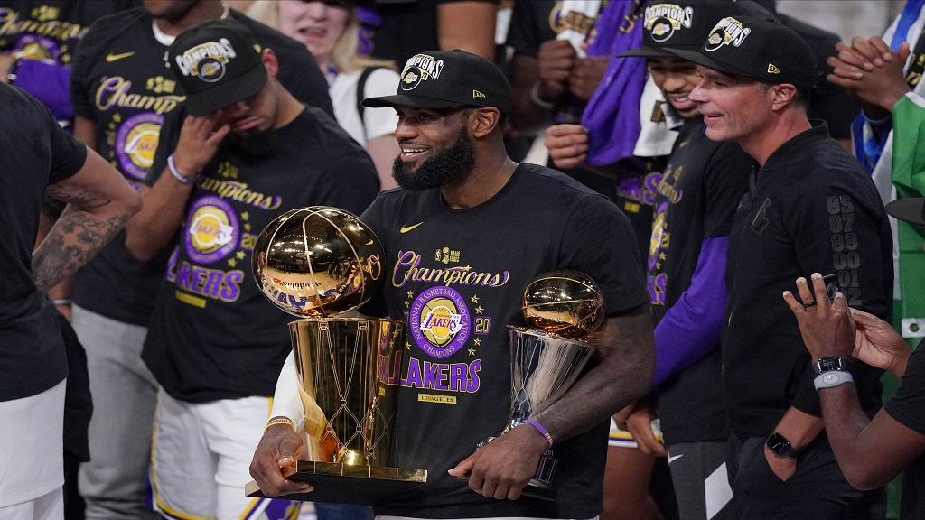 Los Angeles Lakers' LeBron James (23) holds the trophies as he celebrates with his teammates after the Lakers defeated the Miami Heat 106-93 in Game 6 of basketball's NBA Finals on Sunday, Oct. 11, 2020, in Lake Buena Vista, Fla. (AP Photo/Mark J. Terrill).