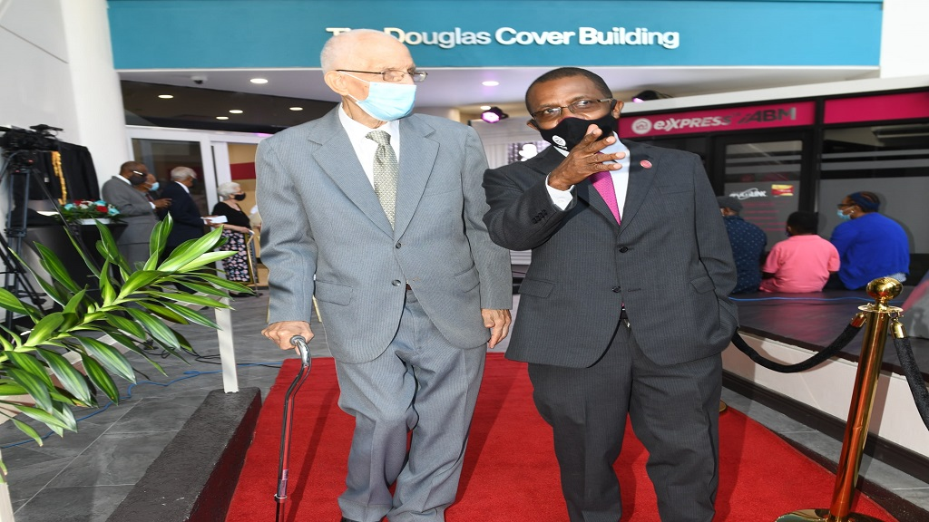 Courtney Campbell (right), President and CEO, Victoria Mutual Group escorts, Douglas Cover, former General Manager, Victoria Mutual Building Society (VMBS), during the official naming ceremony of the Victoria Mutual Chief Office and Duke Street Building, as the 'The Douglas Cover Building'.