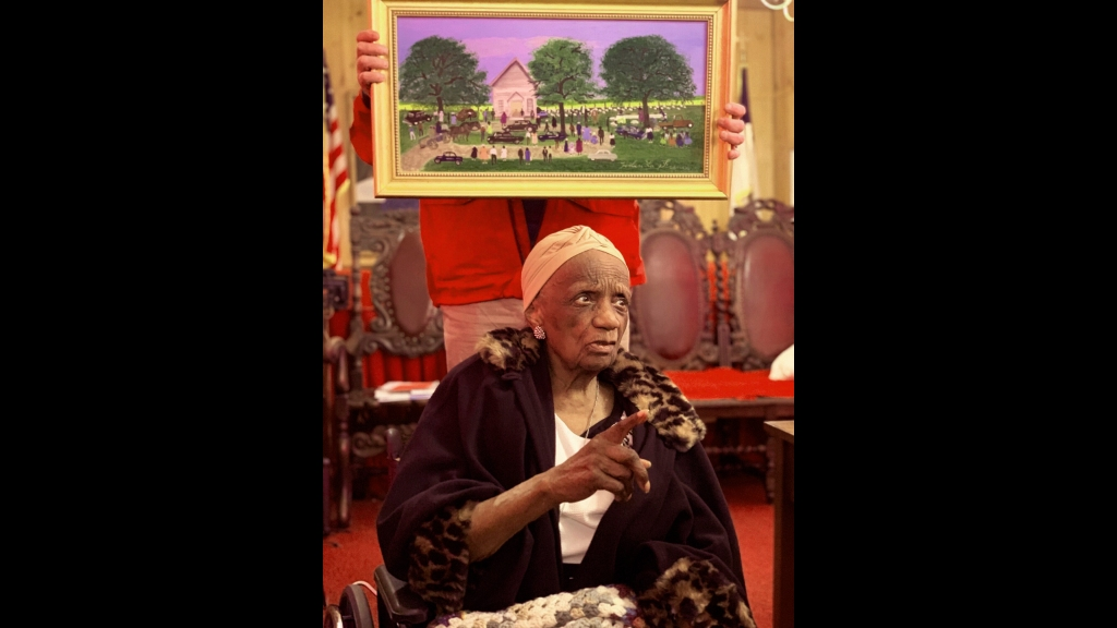 In this photo provided by Bruce Shelton, Painter Helen LaFrance sits under one of her paintings during her 100th birthday party on Saturday, November 2, 2019, in Mayfield, Kentucky. Photo: Bruce Shelton via AP
