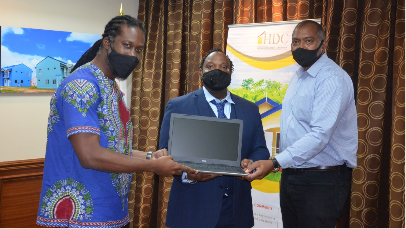Minister in the Ministry of Housing and Urban Development, Adrian Leonce (left) and HDC's Brent Lyons hand over laptops to Member of Parliament for POS South, Keith Scotland.