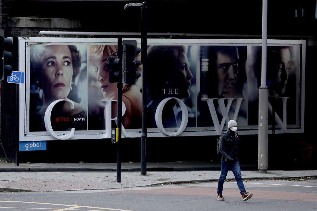 FILE - In this file photo dated Friday, November 20, 2020, a man wearing a face mask walks past a billboard advertising 'The Crown' television series about Britain's Queen Elizabeth II and the royal family, during England's second coronavirus lockdown, in London. (AP Photo/Matt Dunham, FILE)