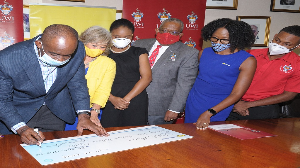 CEO of NCB Financial Group Patrick Hylton signs the symbolic cheque as Chairman of the N.C.B. Foundation, Dr Thalia Lyn; Kimberly Scott, an MBBS graduate and a recipient of a grant from the N.C.B. Foundation; Pro Vice-Chancellor and Principal of the UWI Mona Campus, Professor Dale Webber; CEO of the N.C.B Foundation, Nadeen Mathews-Blair and the UWI Mona Guild President, Sujae Boswell – all look on.
