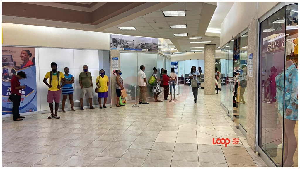 Bajans in a queue to pay bills, (FILE)