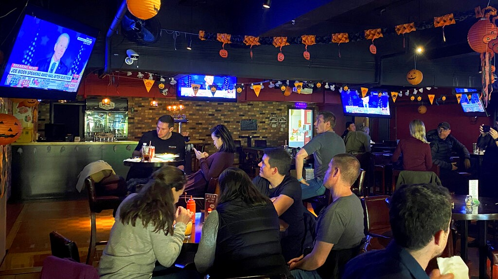 Customers dine while watching a TV showing a live telecast of US presidential candidate Joe Biden speaking during the US election at a pub in Beijing, Wednesday, Nov 4, 2020. (AP Photo/Andy Wong)
