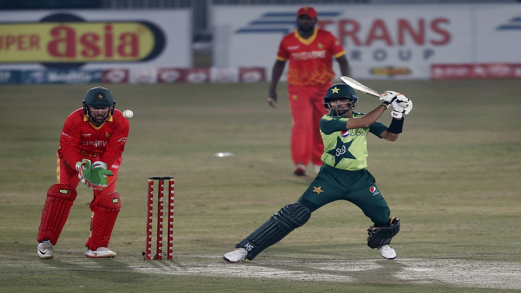 Pakistani batsman Babar Azam, right, plays a shot while Zimbabwe's wicketkeeper Brendan Taylor, left, watches during the 2nd Twenty20 cricket match at the Pindi Cricket Stadium, in Rawalpindi, Pakistan, Sunday, Nov. 8, 2020. (AP Photo/Anjum Naveed).