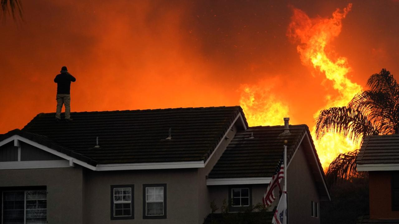 In this Tuesday, October 27, 2020 file photo, Herman Termeer, 54, stands on the roof of his home as the Blue Ridge Fire burns along the hillside in Chino Hills, Calif. (AP Photo/Jae C. Hong)